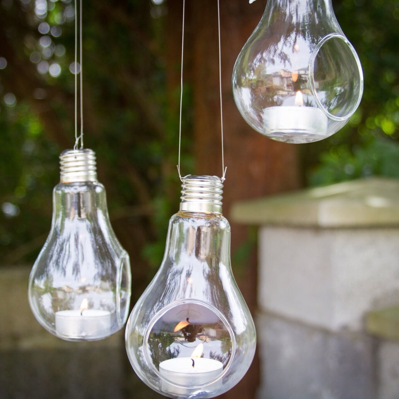 Lit candles inside hanging light bulbs outdoors