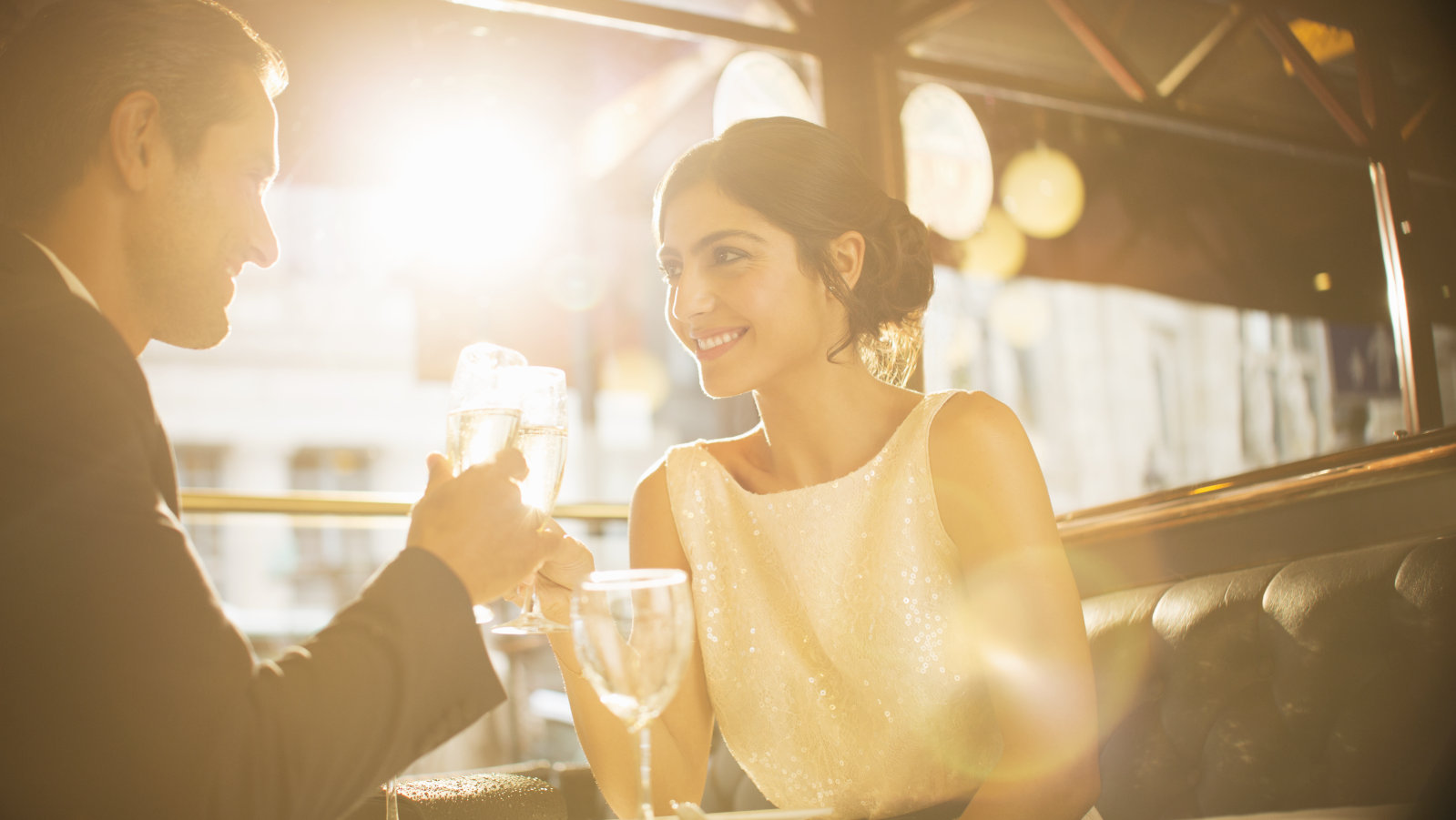 Couple toasting champagne flutes in restaurant